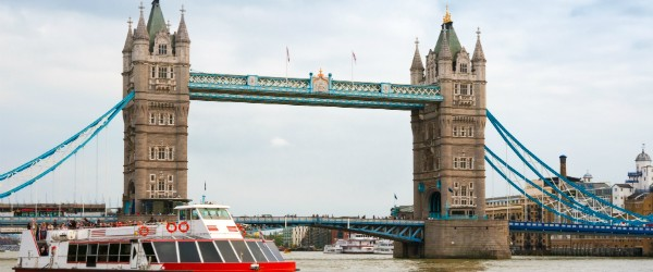 A sightseeing boat goes near the Tower Bridge. London