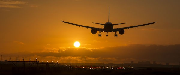 Airplane Landing During Sunrise Featured (Shutterstock.com)